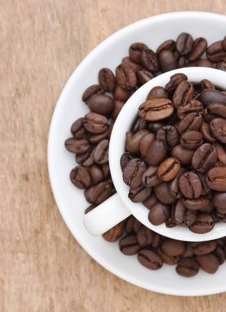 winnower: coffee beans in a cup on a wooden background