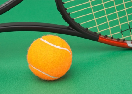 tennis racket and  ball on a green background photo