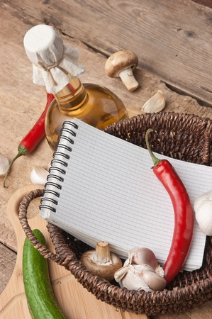 notebook for cooking recipes and vegetables on a cutting board photo