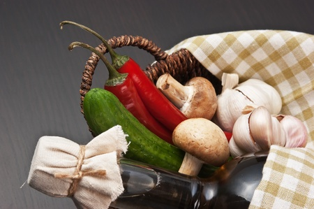 vegetables and a basket with a bottle of vinegar photo