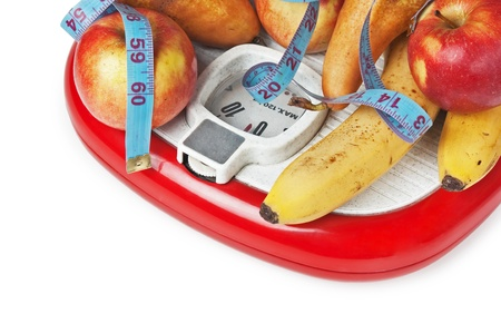 fruit and measuring tape on the floor scales isolated on white photo