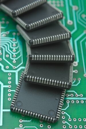electronics industry: pile of microchips on a printed circuit board