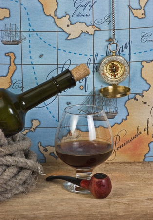 bottle and  glass of wine on background of old maps photo