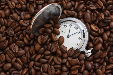 pocket watch in a pile of coffee beans photo