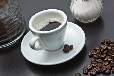 pile of coffee beans and a cup on a gray table photo