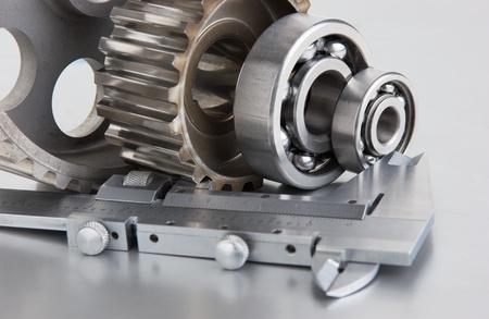 herramientas de mec�nica: engranajes y rodamientos con pinzas sobre una placa de metal