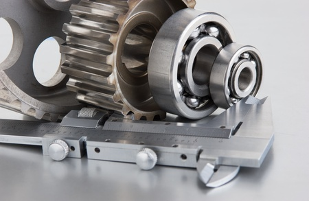 gears and bearings with calipers on a metal plate photo