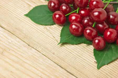 Berry Cherry with leaves on a wooden background photo