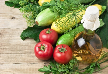 vegetarian: vegetables and a bottle of oil, still life on a wooden table Stock Photo