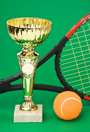 sports awards and  tennis racquets on a green table photo