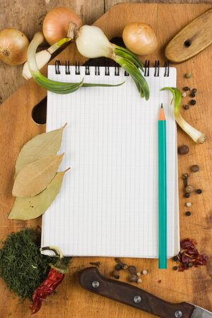 notebook for cooking recipes and spices on a wooden table photo
