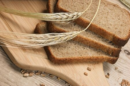 slices of rye bread and ears of corn on the wooden table photo