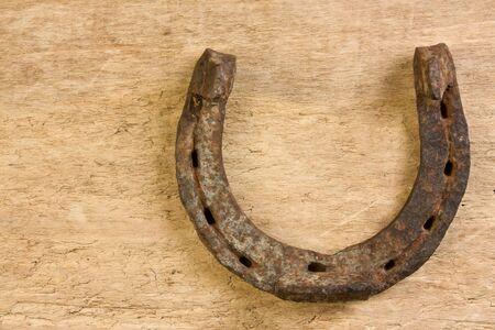old rusty horseshoe on a wood background photo