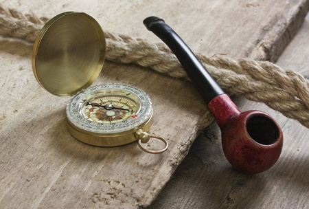 old tobacco pipe and compass on a wooden background photo