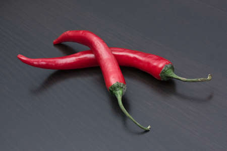 Two red chili peppers on the kitchen table photo