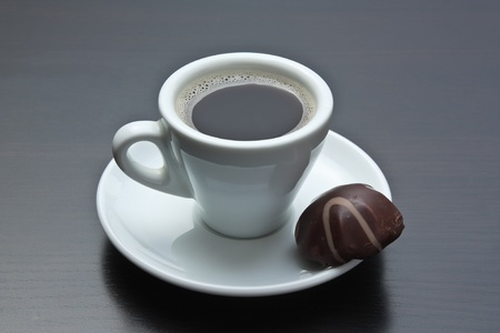 candy shop: cup of coffee and chocolate candy on table