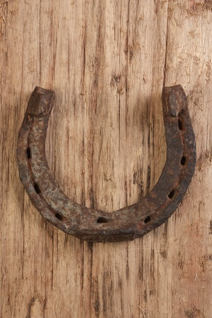 old rusty horseshoe on a wood background photo