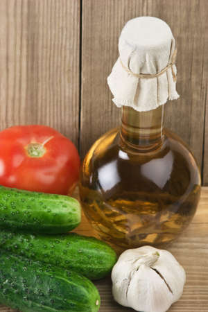 vegetables and a bottle of oil, still life on a wooden table photo