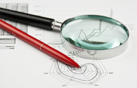magnifying glass and working paper with  diagram  photo