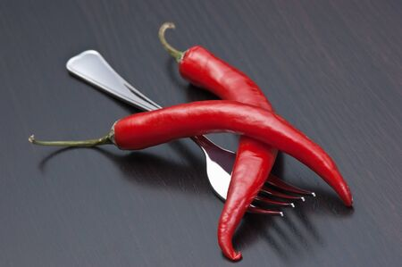 Two red chili peppers and fork on the kitchen table photo