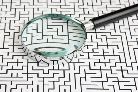 unravel: magnifying glass on the background of the labyrinth