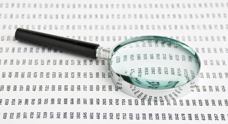 magnifying glass on a document with columns of figures Stock Photo - 11424074