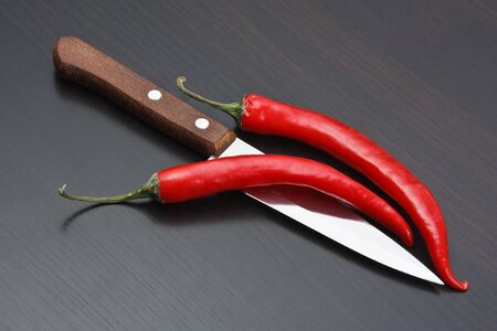Two red chili peppers and knife on the kitchen table photo