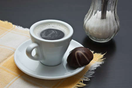 hot coffees: cup of coffee and chocolate candy on table