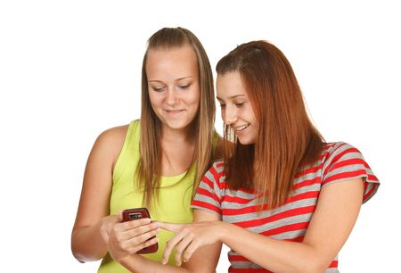 Portrait of lovely young women using mobile phone together  isolated on white photo
