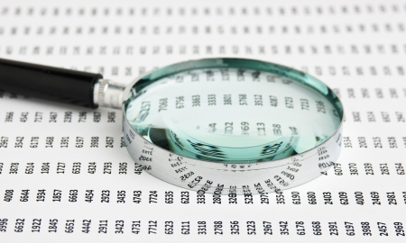 financial item: magnifying glass on a document with columns of figures Stock Photo