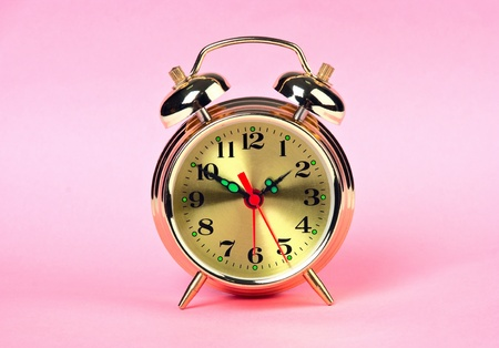golden alarm clock on a color background, theme time photo