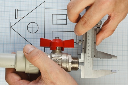 plumbing fittings in hand on the drawing photo