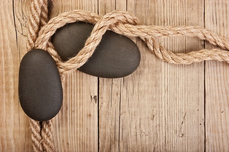 pebble and rope on a wooden background photo