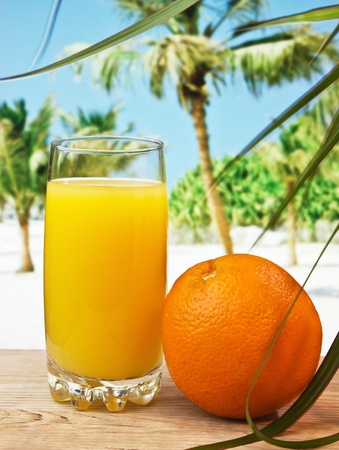 Glass of orange juice on a beach table  Stock Photo - 12540197
