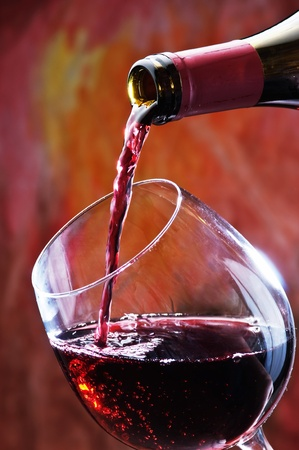 Red wine being poured into wine glass photo
