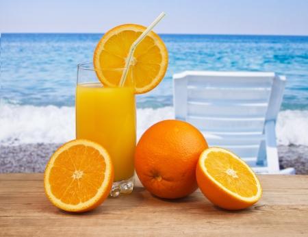 tabla de surf: Vaso de jugo de naranja en una mesa de playa