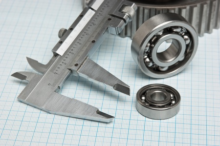 caliper with gears and bearings on graph paper photo