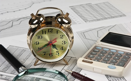 gold clock and office supplies on the table photo