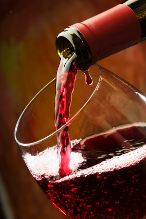 abstract liquor: Red wine being poured into wine glass Stock Photo