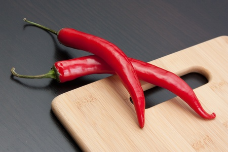 Red chili peppers on a cutting board photo