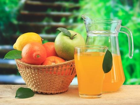 verre de jus: corbeille de fruits et de jus sur une table en bois dans le jardin