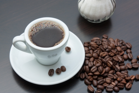 hot coffees: pile of coffee beans and a cup on a gray table