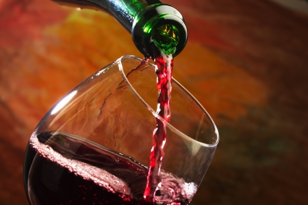 pouring wine: Red wine being poured into wine glass Stock Photo