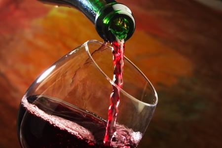 bouteille de vin: Vin rouge �tant vers� dans un verre de vin