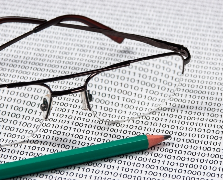 glasses and  pencil on the background of a binary code photo