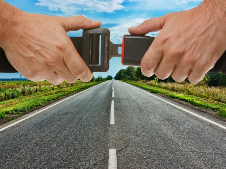 cinturon seguridad: manos botón del cinturón de seguridad en el fondo de la carretera