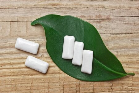 chewing gum and green leaf on a wooden background photo