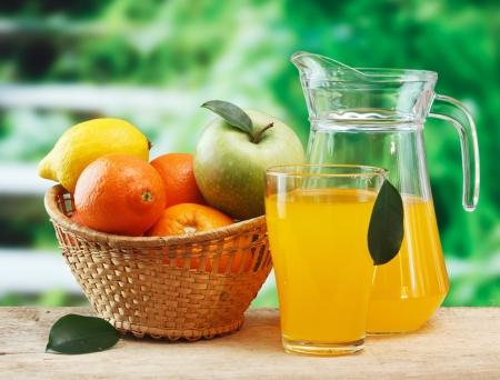 variedad de frutas y jugo en una mesa de madera en el jardín