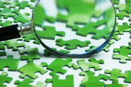 magnifying glass: magnifying glass on the green puzzle Stock Photo