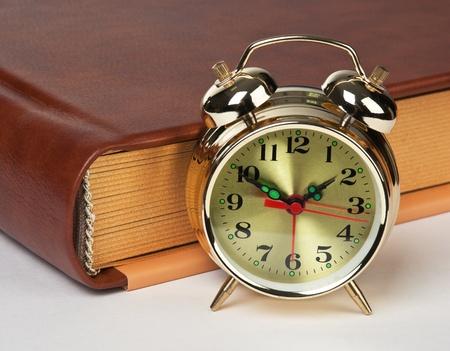 Reloj de alarma de oro en el libro aislado en un fondo blanco Foto de archivo - 15332677